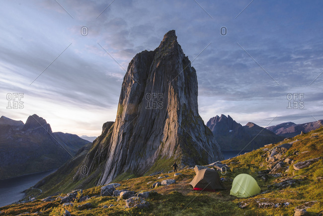 Norway, Senja, Man and two tents near Segla mountain at sunset
