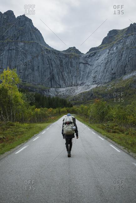 Norway, Lofoten Islands, Backpacker walking down road in mountain landscape