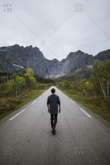 Norway, Lofoten Islands, Man walking down road in mountain landscape