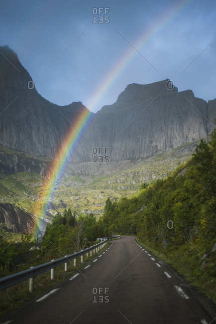 Norway, Lofoten Islands, Rainbow above empty road in mountain landscape