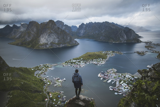 Norway, Lofoten Islands, Reine, Man looking at fjord from Reinebringen mountain