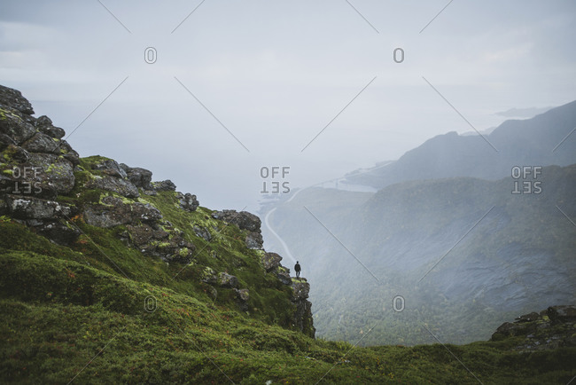Norway, Lofoten Islands, Reine, Man looking at view from Reinebringen mountain during rain