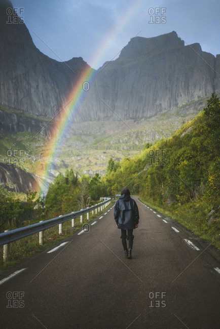 Norway, Lofoten Islands, Man walking down road with mountains and rainbow in background