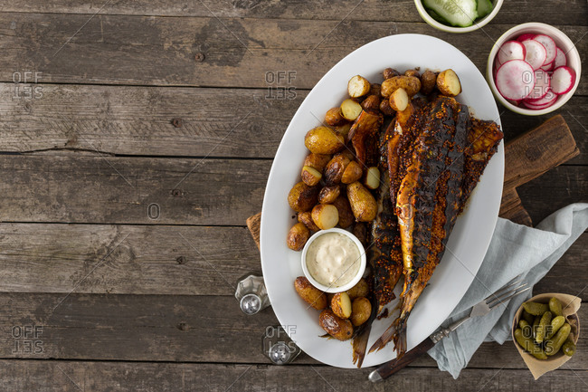 Healthy dinner with grilled mackerel, new potatoes and vegetable on wooden table with copy space