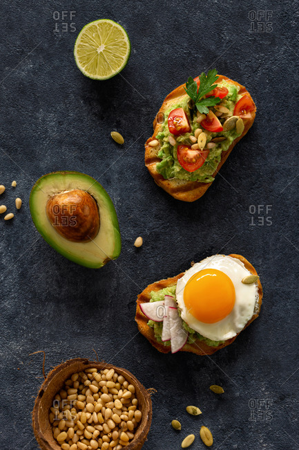 Set of different sandwiches with avocado cream, fried egg, tomato, nuts and seeds top view