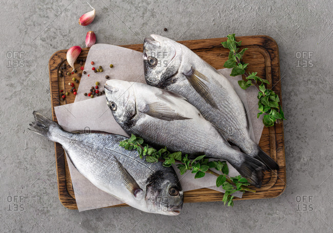 Raw fish dorada or sea bream on cutting board with ingredients for cooking