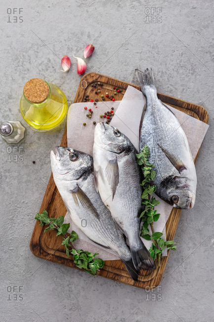 Raw fish dorada or sea bream with ingredients for cooking on the grill