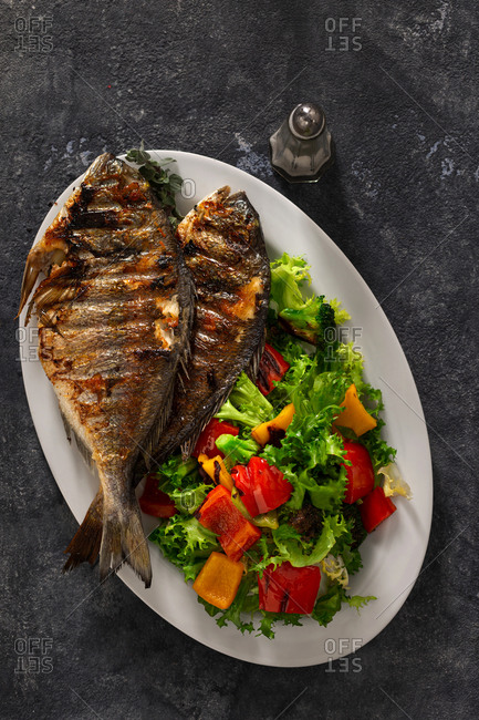 Plate of fried dorado and fresh salad on dark background top view