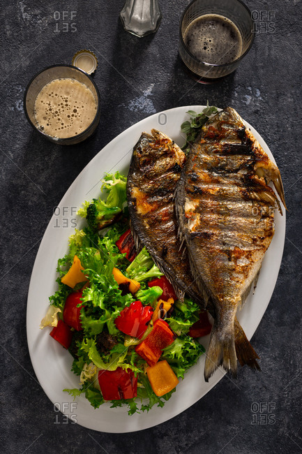 Plate of fried dorado and fresh salad on dark background with glass dark beer top view