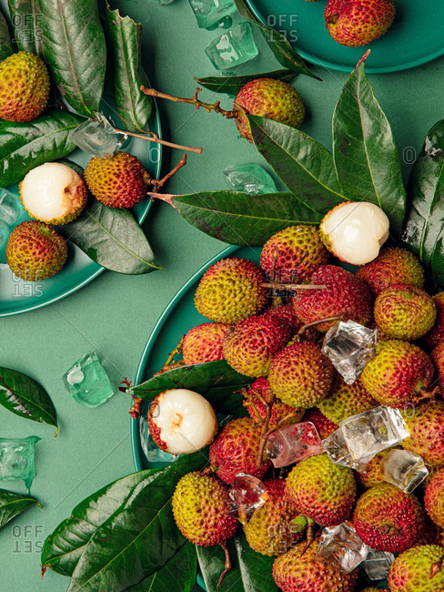 Overhead view fresh lychee on green background.