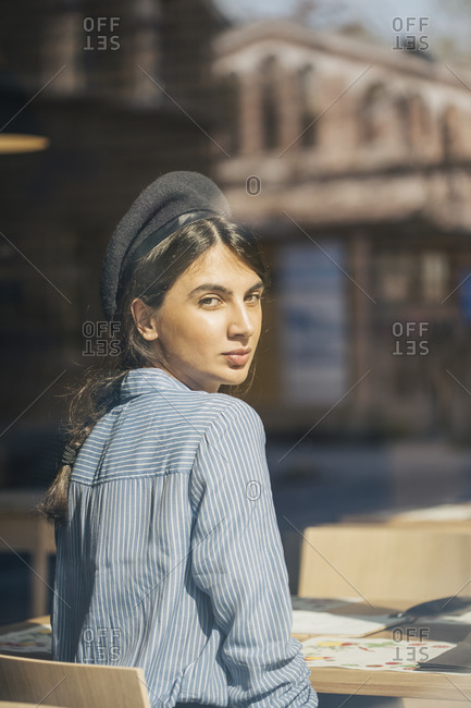 Confident girl looking aside sitting in the coffee shop window