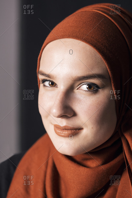 Portrait of a young adult Muslim female wearing brick orange hijab, looking to camera