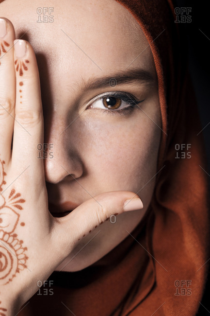 Portrait of a young adult Muslim female wearing brick orange hijab, half face covered with hand, close up