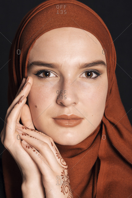 Portrait of a young adult Muslim female wearing brick orange hijab, looking serious close up