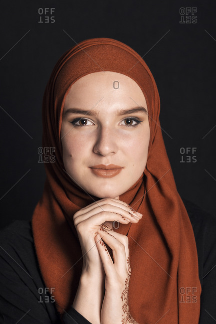 Portrait of a young adult Muslim female wearing brick orange hijab, holding hands under chin