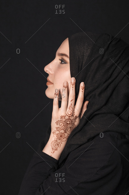 Portrait of a young adult Muslim female wearing black hijab, henna tattoo looking aside, against black wall