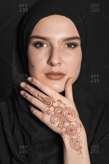 Portrait of a young adult Muslim female wearing black hijab, henna tattoo looking serious with hand on he chin