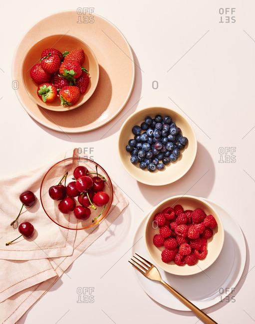Various Berries in Bowls on Pink
