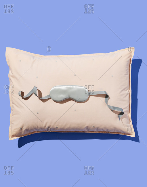 Silver Eye Mask on Pink Pillow