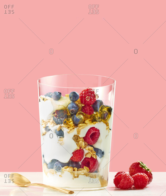 Berry Parfait with Honey and Granola on Pink Background