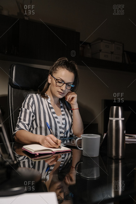 Beautiful woman working at home at night.