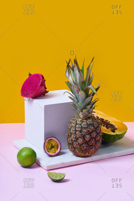Still life with summer fruits and white cube on colorful background