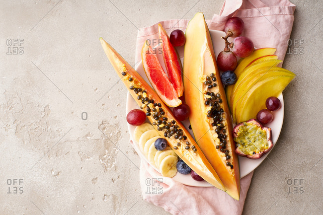 Colorful tropical summer fruits and berries. Papaya, mango, passion fruit, banana, grapes sliced and served on a plate. Summer fruits platter