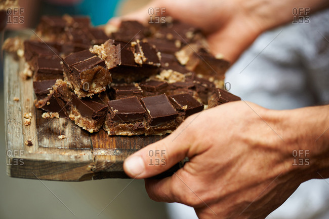 A man holding a wooden board with pieces of chocolate and caramel covered shortbread