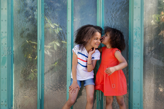 Sisters whispering secrets at each other in front of a green wall