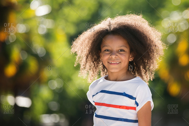 Smiling portrait of a beautiful tween girl with afro hair in a park