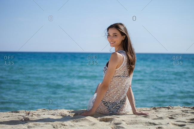 Young woman with long brown hair sitting on sandy beach, smiling at camera.
