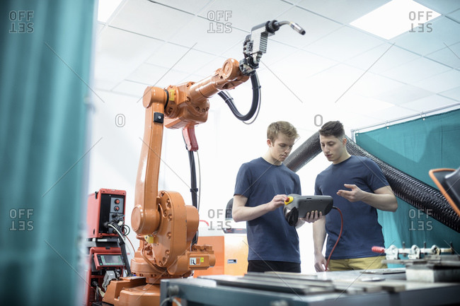 Two male engineers controlling robotic welder in factory.
