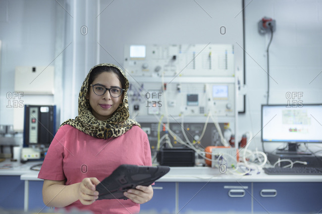 Female electrical engineer standing in front of electrical supply test rig in research facility.
