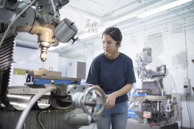 Female engineer working with drill in engineering factory.