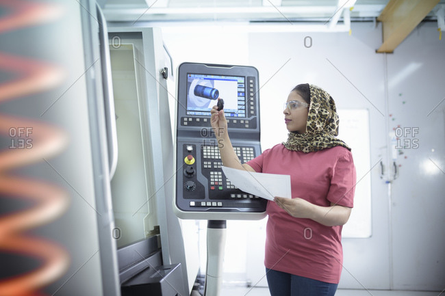 Female engineer inspecting CNC lathe in factory.