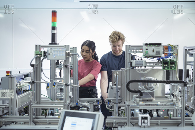 Male and female trainee engineers inspecting robotic assembly line in research facility.