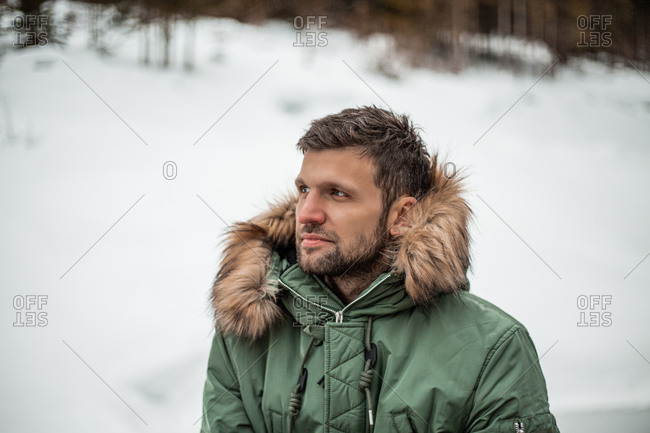 A man wearing a green coat with fur trimmed hood standing in a snowy landscape.