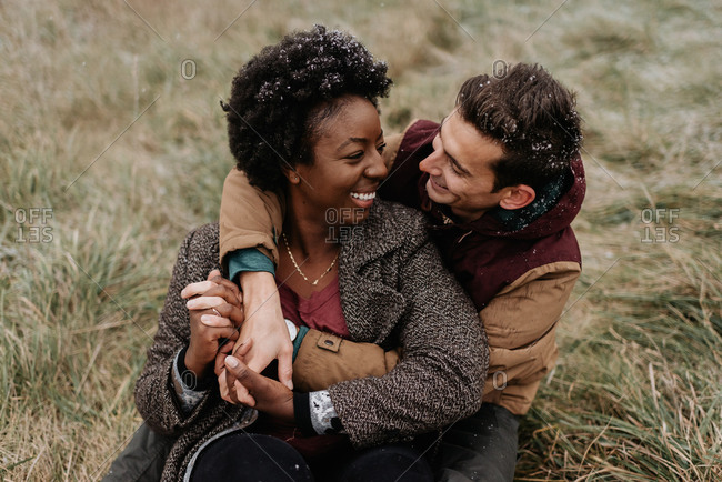 A black woman and white man hugging each other and smiling, sitting in a field of grass.