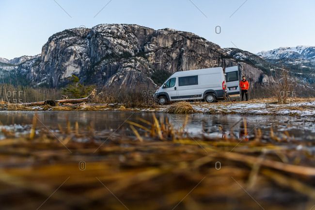 Man wearing an orange jacket by a camper van in a rocky landscape.