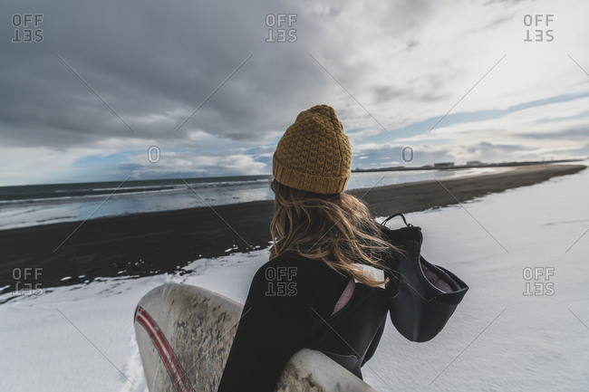 Rear view of a woman wearing a wetsuit and holding a surfboard standing on a snowy beach looking out to sea.