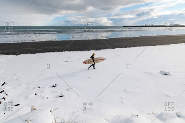 Woman wearing a wetsuit and holding a surfboard walking along a snowy beach.