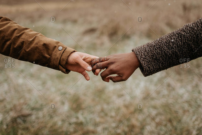 Interracial couple, man and woman holding hands, one wearing a gold wedding ring.