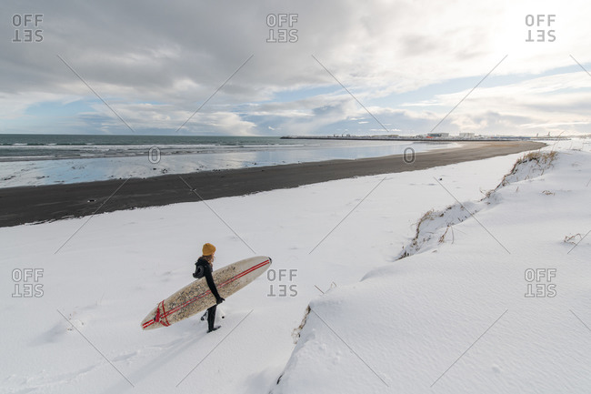 Rear view of a woman wearing a wetsuit and holding a surfboard walking along a snowy beach.