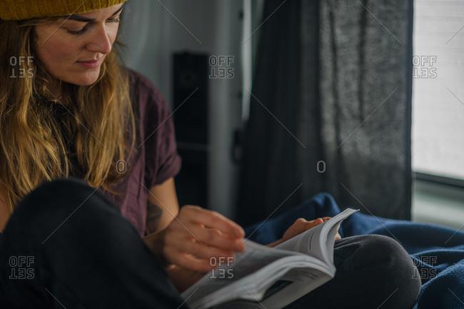 A woman reading a book in a camper van. Winter road trip.