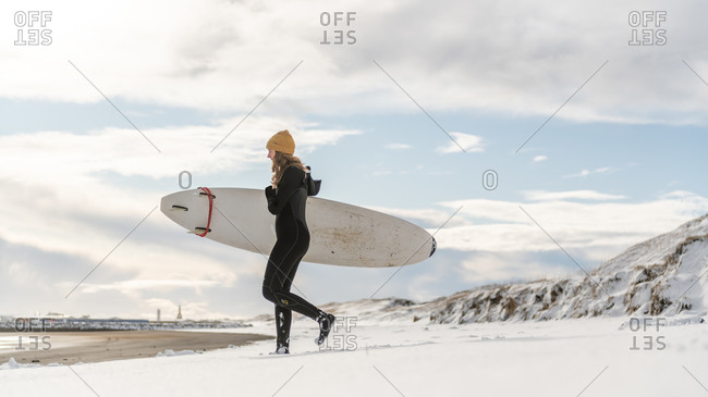 A woman wearing a wetsuit and holding a surfboard walking down a snowy beach and looking out to sea.