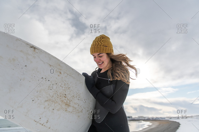 A woman wearing a wetsuit and carrying a surfboard walking along a snowy beach.