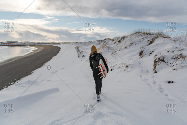Rear view of a woman wearing a wetsuit and holding a surfboard walking on a snowy beach.