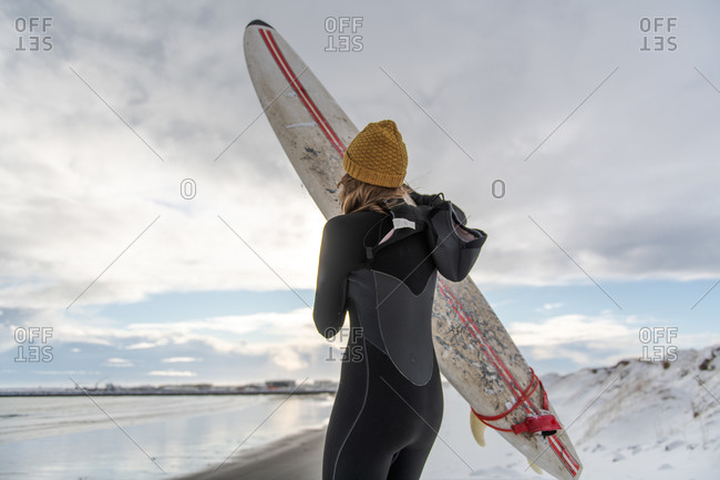 Rear view of a woman wearing a wetsuit and holding a surfboard standing on a snowy beach and looking out to sea.