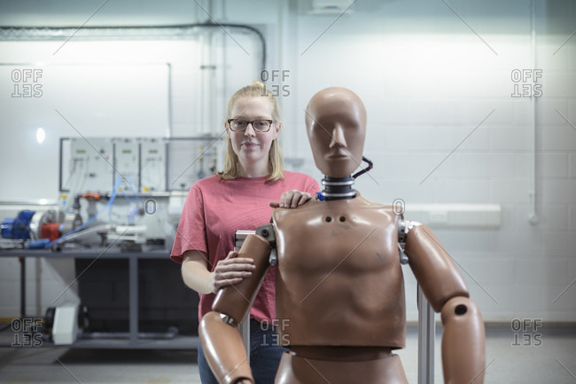 A female student standing behind a test dummy in a workshop.