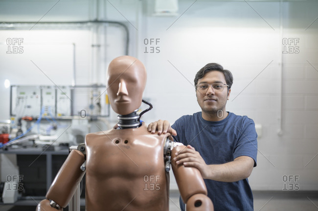 A male student standing behind a test dummy in a workshop.